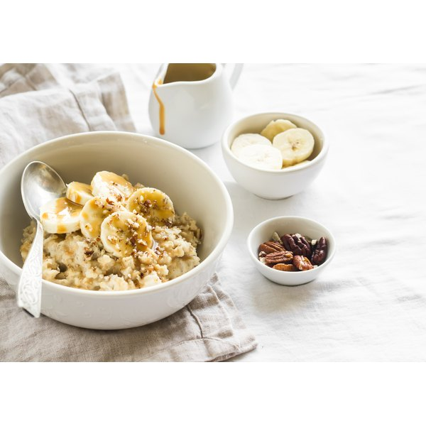 A bowl of oatmeal topped with banana slices on a table.