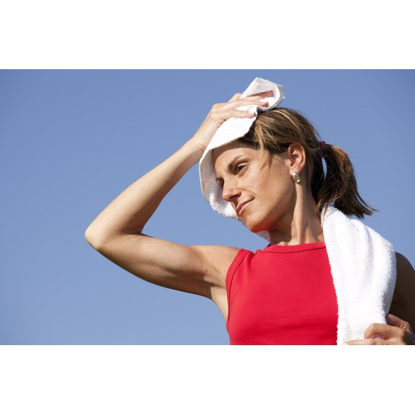 A fit woman is wiping sweat off her forehead.