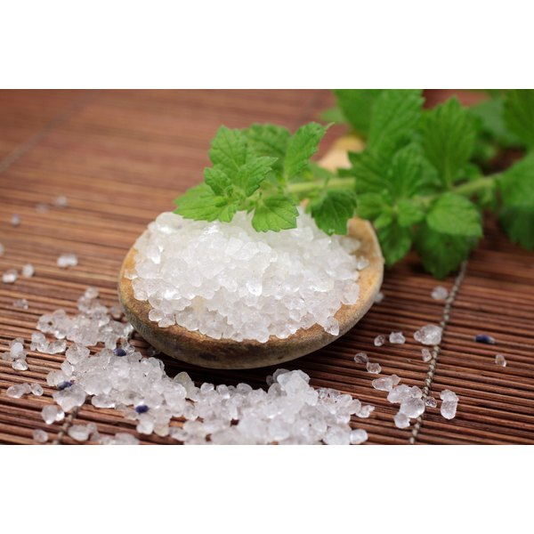 A spoonful of sea salt with a sprig of fresh mint on a bamboo mat.