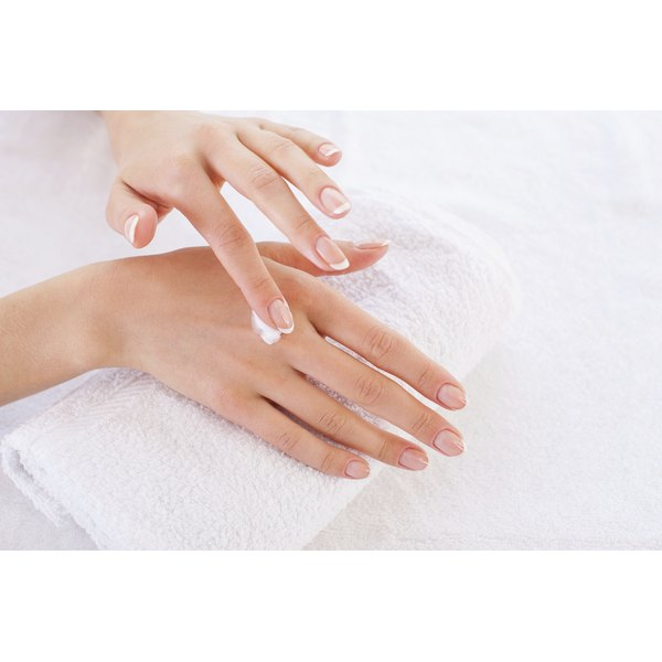 Close-up of a woman applying hand lotion to her hands.