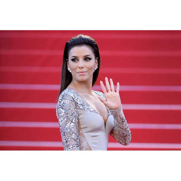 Eva Longoria waving on the red carpet.