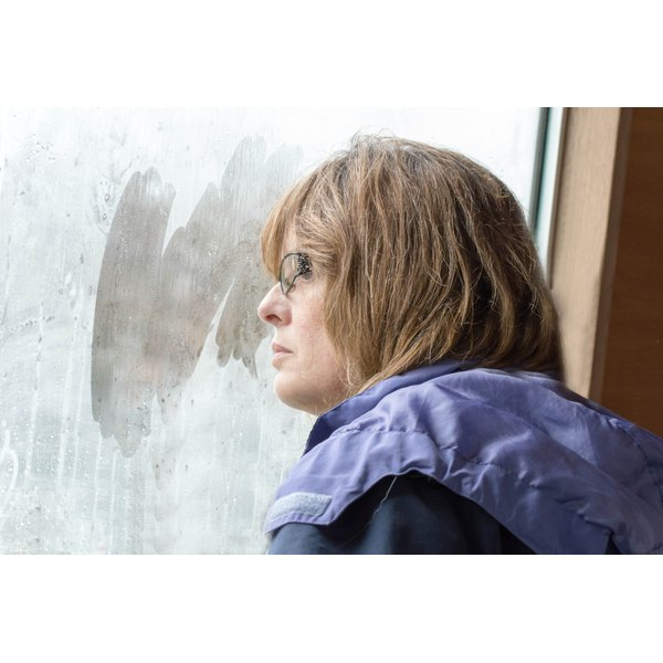 Mature woman looking out window showing her from profile.