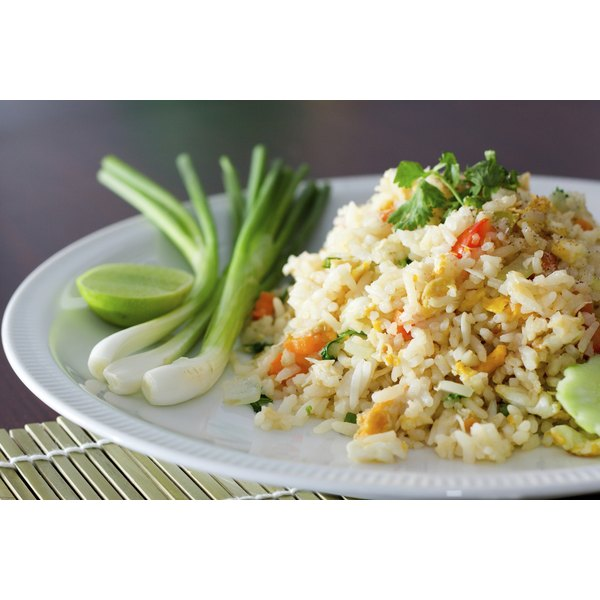 A plate of Chinese vegetable fried rice served with scallions, cilantro and a lime wedge.