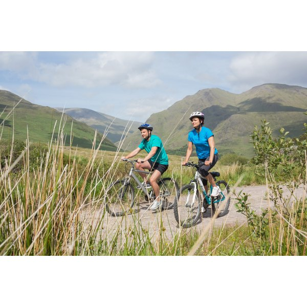 Two people are cycling in the mountains.