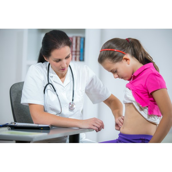 A doctor examining a young girls abdomin.