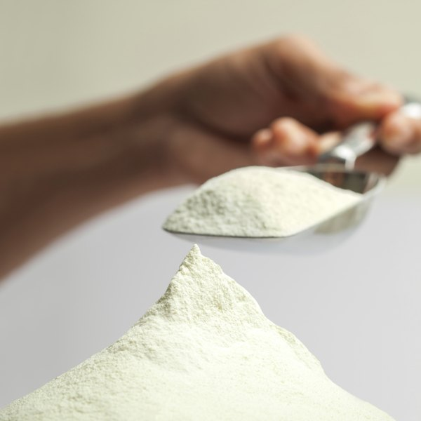 Person lifting calcium lactate powder with a scoop.