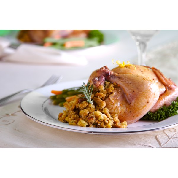 A cornish hen stuffed with Stove Top stuffing on a plate at the table.