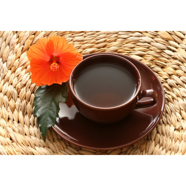 A cup of hibiscus tea next to a hibiscus flower on a woven mat.