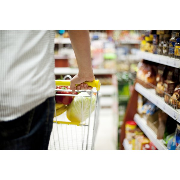 A man with a cart selecting items in the grocery store.