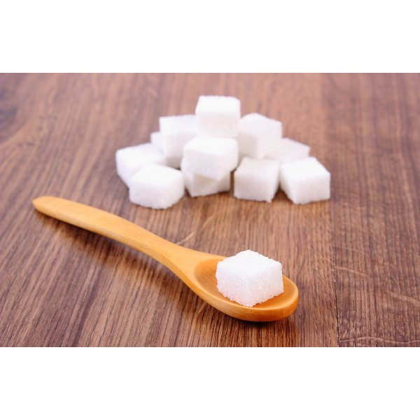 A sugar cube on a wooden spoon.