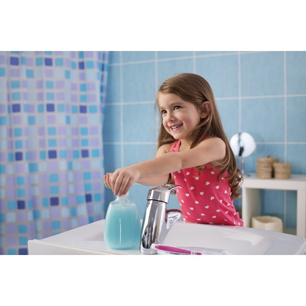 Little girl happily washing her hands.