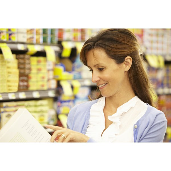 A woman is reading a nutritional label on a box.