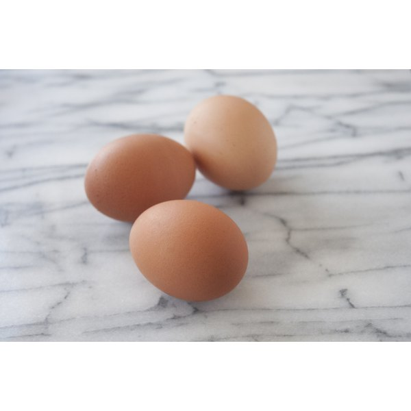 Brown eggs on a marble counter.