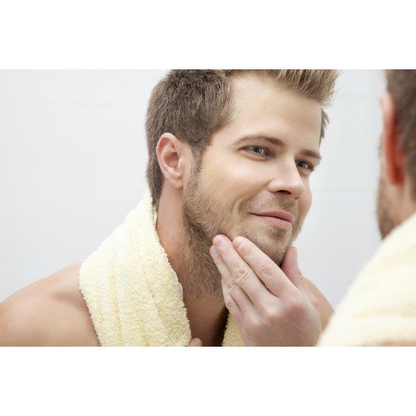 Man looking at his beard in a mirror.