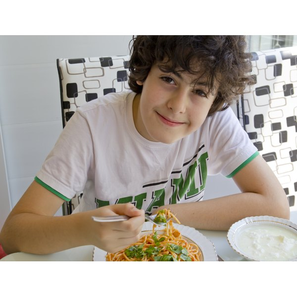 A teenager eating a bowl of spaghetti at a kitchen table.