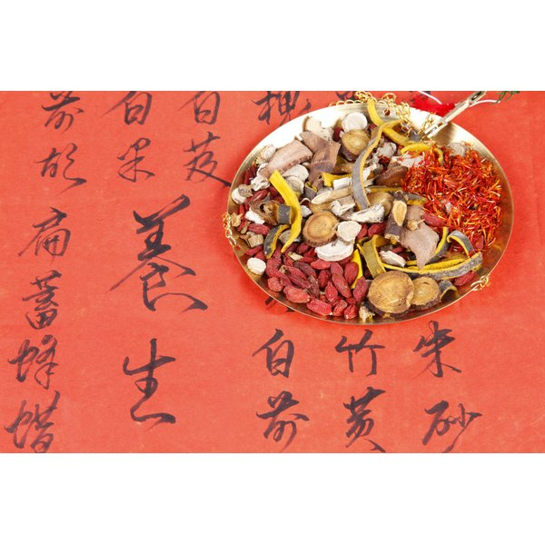 A plate of Chinese medicine's sit on a piece of paper with Chinese handwriting on it.