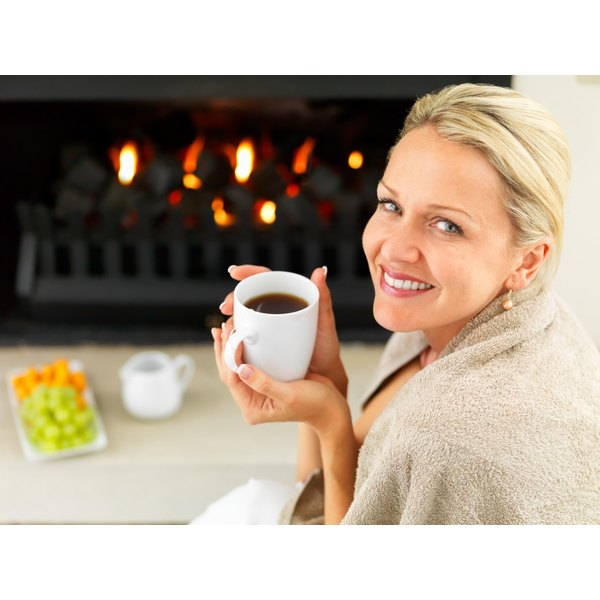 fresh faced woman drinking coffee in front of fire place