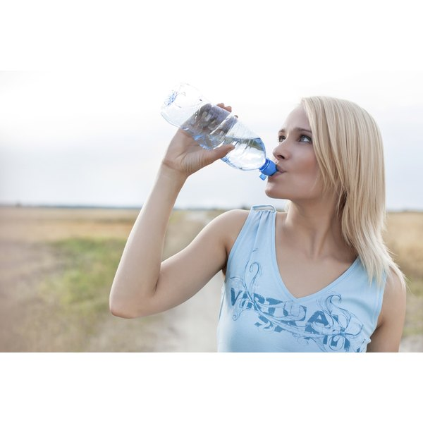 Woman drinking from water bottle outside
