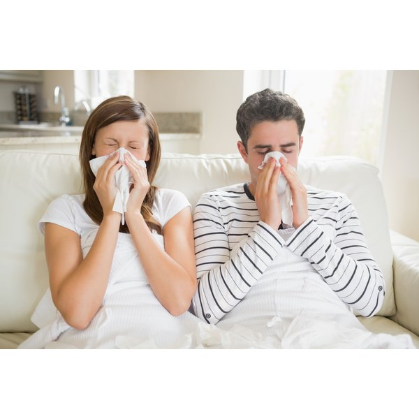 A woman and man are lying in bed with flu like symptoms.