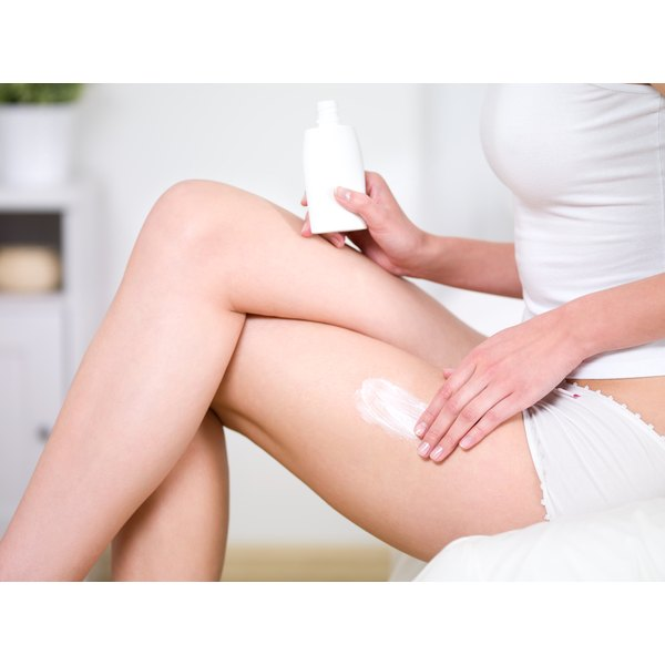 Woman applying cellulite cream to her thighs.