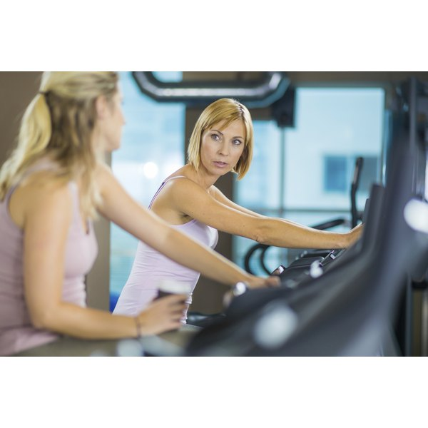 Two women are using the elliptical machines.
