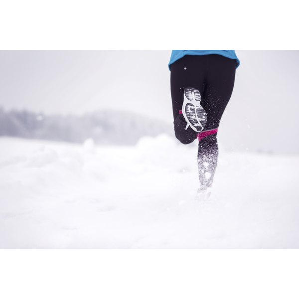 A woman's legs and feet while jogging through snow.