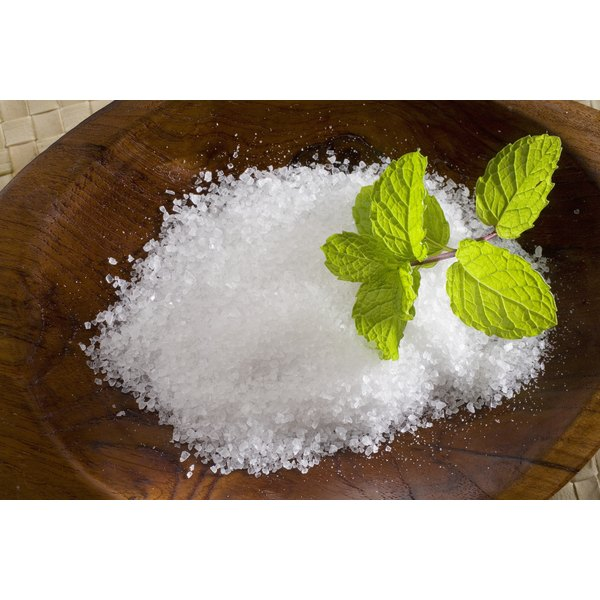 A wooden dish with salt and a sprig of mint on top.