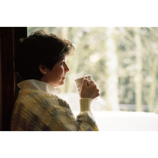 A young woman drinks a cup of tea while looking outside.