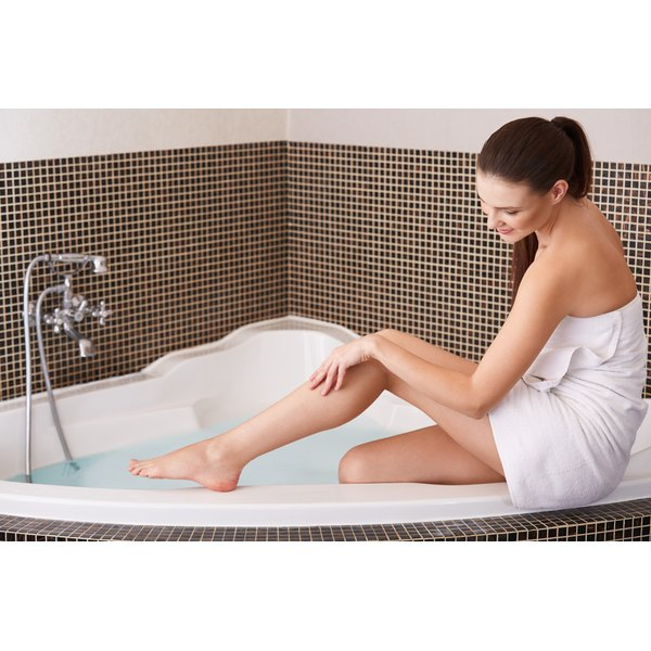 A woman is moisturizing her legs in the bath tub.