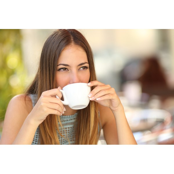 A woman is drinking a cup of coffee or an espresso.