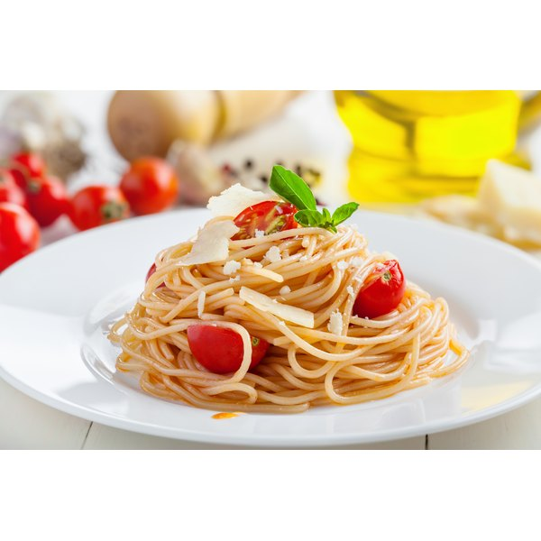 A plate of pasta with tomatoes and shaved parmesan cheese and to.