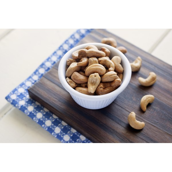 A bowl of cashew nuts on a cutting board.