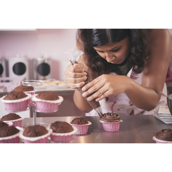 A woman adds frosting to her cupcakes.
