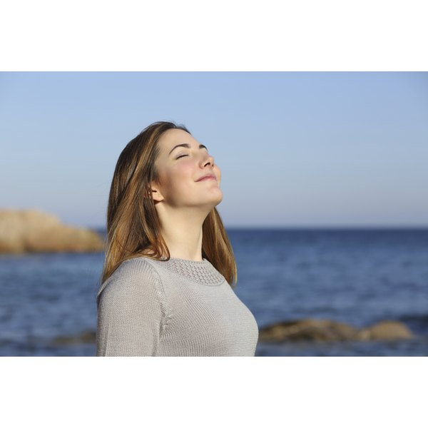 A woman breathing in fresh air on the beach.