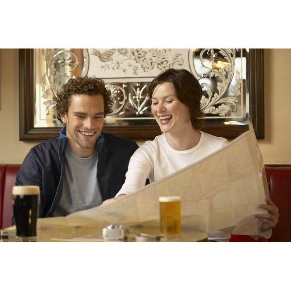 A couple is sitting in a pub together drinking beer.