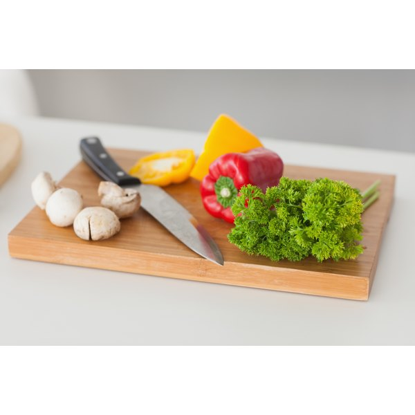 Parsley on a chopping board next to some vegetables.