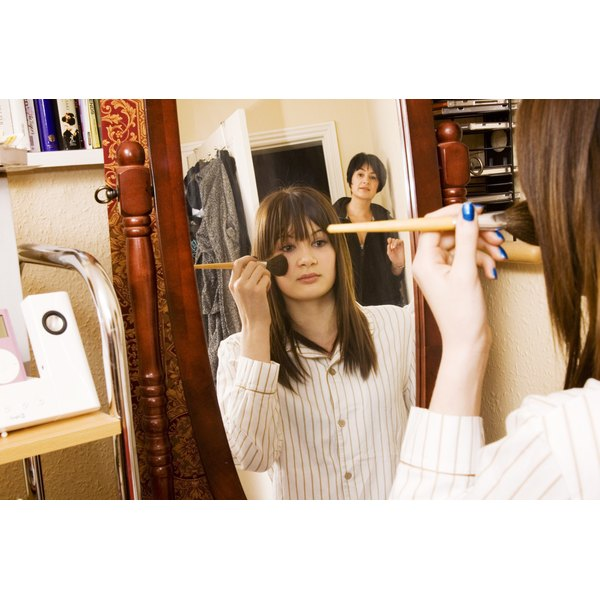 A girl with long hair applies make up in her room as her mother comes in the room.