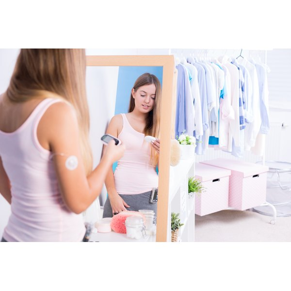 A teenage girl standing in a mirror holding a diabetic meter.