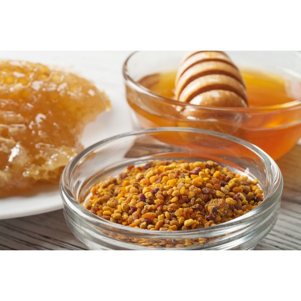 A honey dipper in a bowl of honey on a table with a honeycomb and bee pollen.