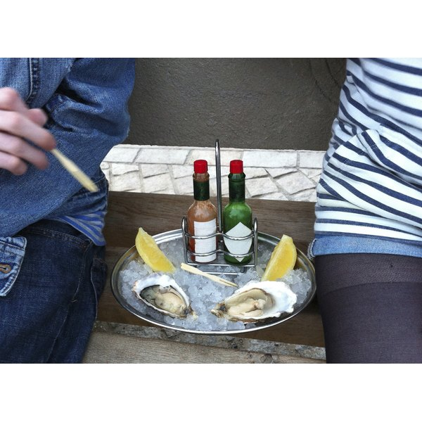 A couple eating oysters with Tabasco sauce on a bench.