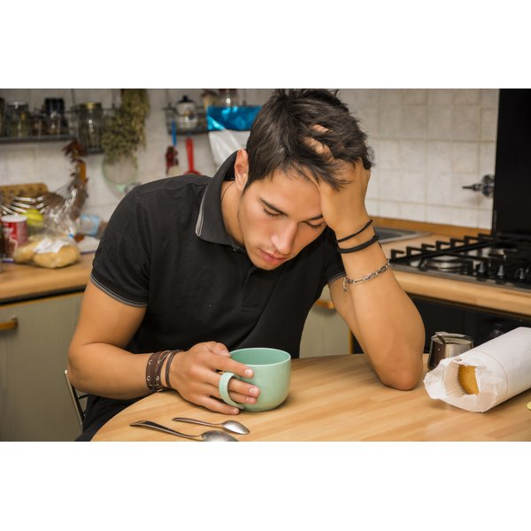 A man with his head propped in his hand looks nauseous as he sits at the kitchen table.