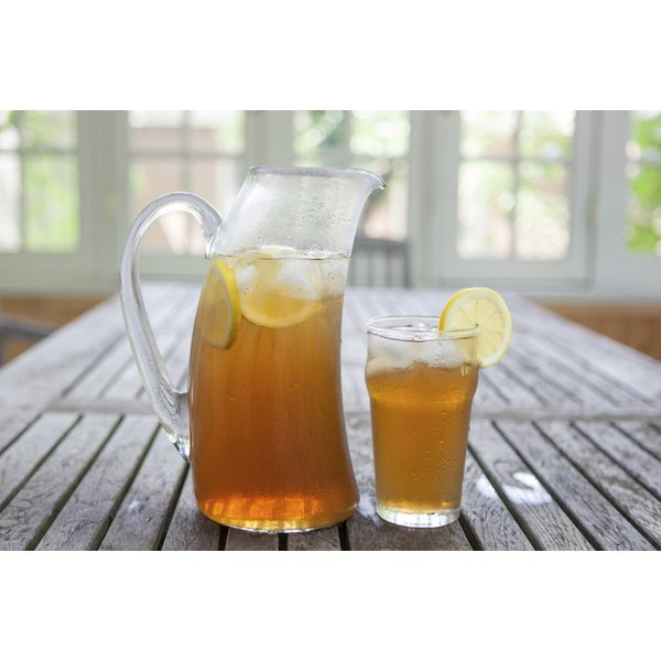 A glass and pitcher of iced tea with lemon on a table.