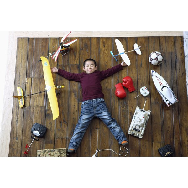 A child laying on the floor surrounded by toys.