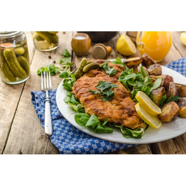 A plate with pork schnitzel and potatoes on a wooden table.