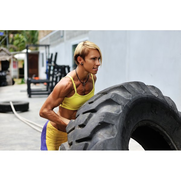 A woman is flipping a huge tire.
