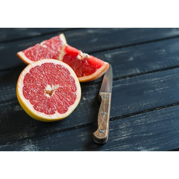 A sliced grapefruit on a wooden table.