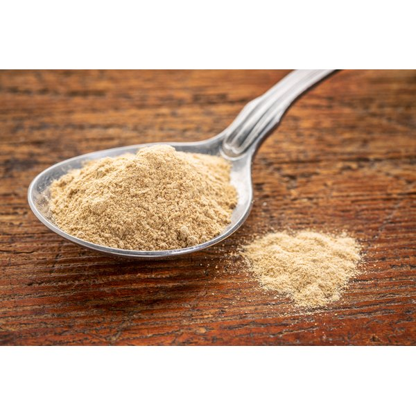A spoonful of maca root powder on wood.