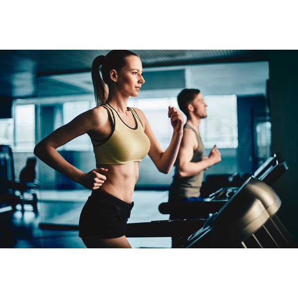 A man and woman workout on treadmills at a gym