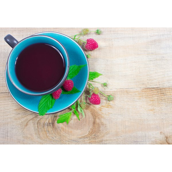 A cup of raspberry tea on a wood surface.