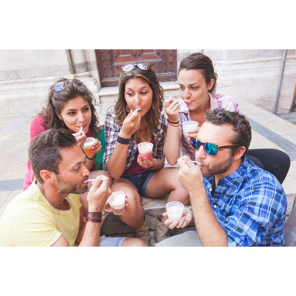 A group of friends eating snow cones outside.